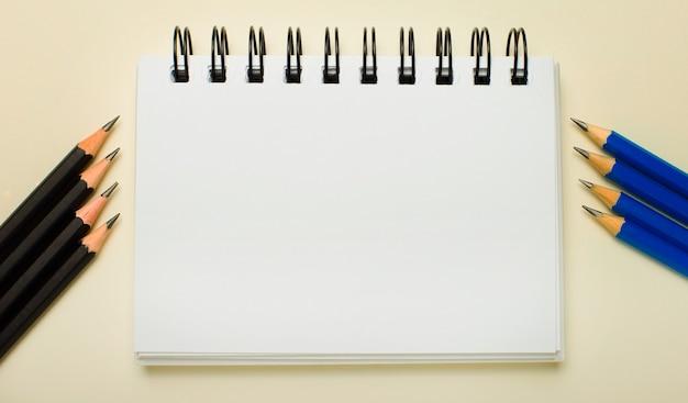明るい背景に、テキストやイラストを挿入する場所のある白いノートと、側面に黒と青の鉛筆。レンプレート