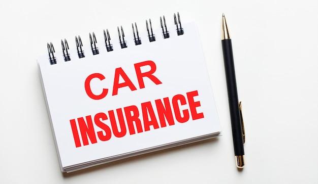 На светлом фоне белая записная книжка со словами страхование автомобиля и ручка.