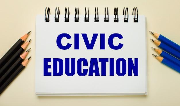 明るい背景に、civiceducationというテキストと側面に黒と青の鉛筆が付いた白いノート。