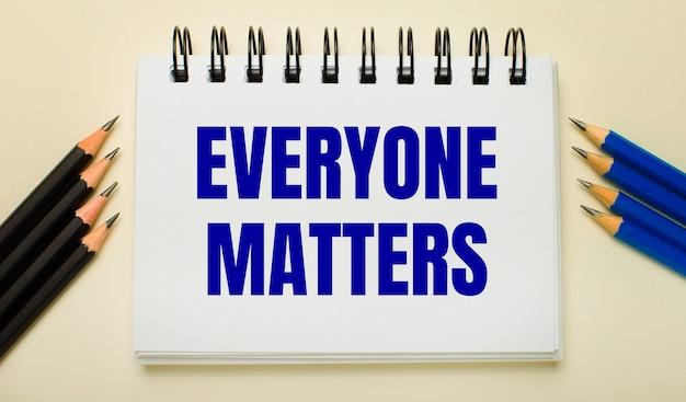 밝은 배경에 everyone matters라는 텍스트가 있는 흰색 공책과 측면에 검정 및 파랑 연필이 있습니다.