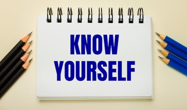 明るい背景に、「know yourself」というテキストがあり、側面に黒と青の鉛筆が付いた白いノート。
