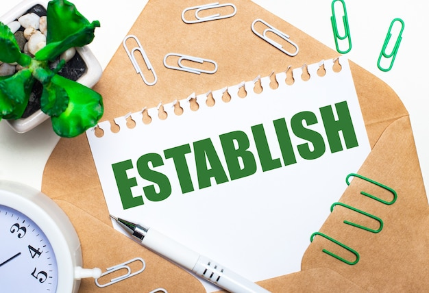 На светлом фоне открытый конверт, белый будильник, зеленое растение, белые и зеленые скрепки, белая ручка и лист бумаги с текстом establish.