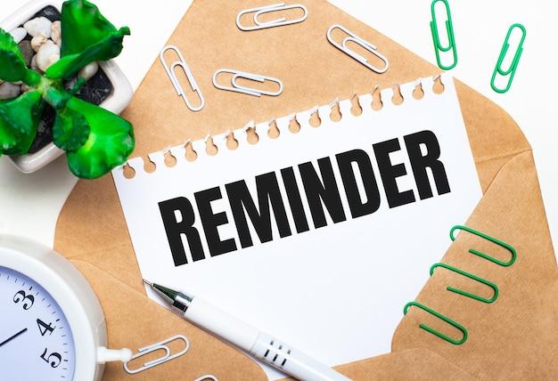 밝은 배경에 열린 봉투, 흰색 알람 시계, 녹색 식물, 흰색 및 녹색 종이 클립, 흰색 펜 및 reminder 텍스트가있는 종이 한 장