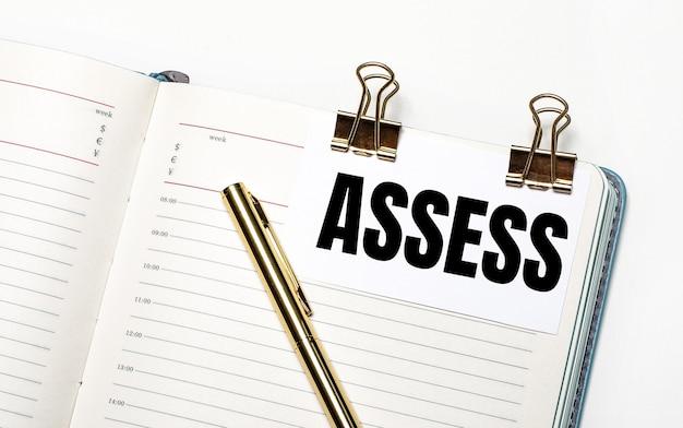 На светлом фоне открытая тетрадь, лист бумаги с золотыми зажимами и текстом assess и золотая ручка. вид сверху. бизнес-концепция