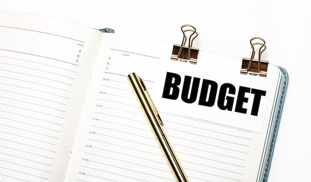 밝은 배경에 열린 노트북, 금 클립이있는 종이, budget 텍스트 및 금 펜. 위에서 봅니다. 비즈니스 개념