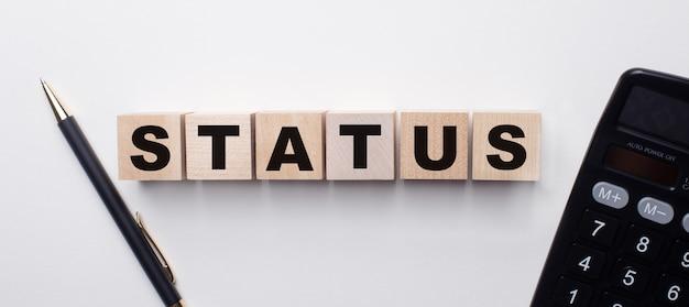 電卓とペンの間の明るい背景には、statusという単語が付いた木製の立方体があります
