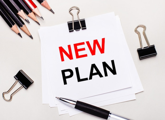 На светлом фоне черные карандаши, черные скрепки, ручка и лист белой бумаги с текстом new plan.