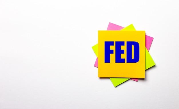 На светлом фоне - яркие разноцветные наклейки с текстом fed. копировать пространство