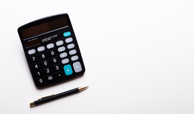 На светлом фоне калькулятор и ручка. скопируйте пространство. вид сверху