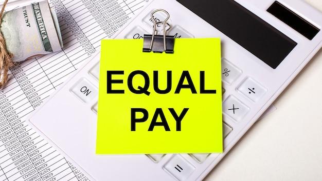 На светлом фоне - наличные, белый калькулятор и желтая наклейка под черной канцелярской скрепкой с текстом equal pay. бизнес-концепция