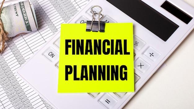 明るい背景-現金、白い電卓、黒いペーパークリップの下にある黄色のステッカーと「financialplanning」というテキスト。ビジネスコンセプト