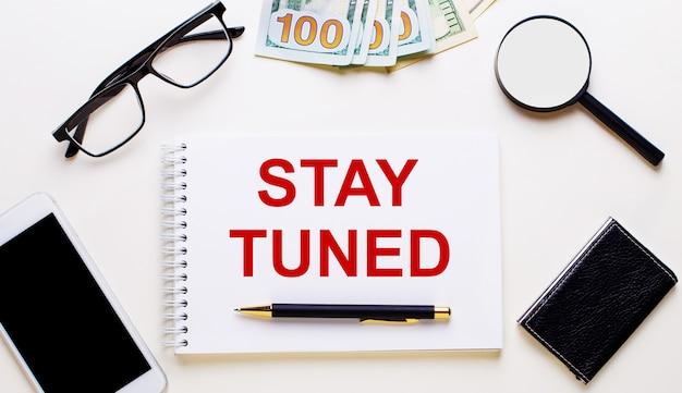 На светлом фоне доллары, очки, лупа, телефон, ручка и блокнот с надписью stay tuned.