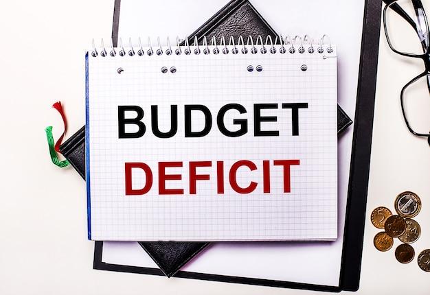 明るい背景のメガネ、コイン、および予算の赤字が刻まれたノートブック