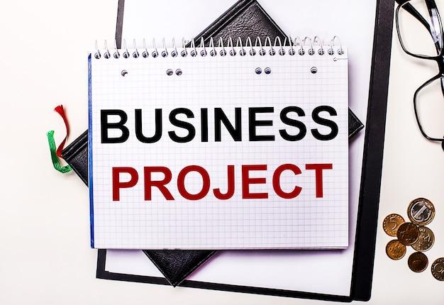 明るい背景のメガネ、コイン、そしてbusinessprojectと書かれたノート。ビジネスコンセプト