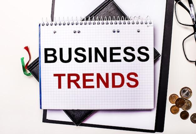 На светлом фоне очки, монеты и блокнот с надписью бизнес тенденции. бизнес-концепция