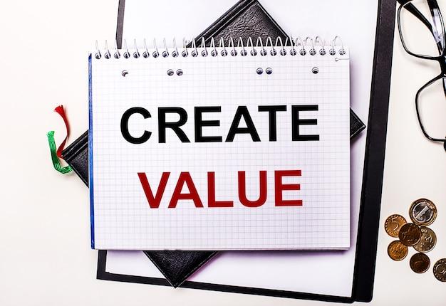 明るい背景のメガネ、コイン、createvalueと書かれたノート。ビジネスコンセプト