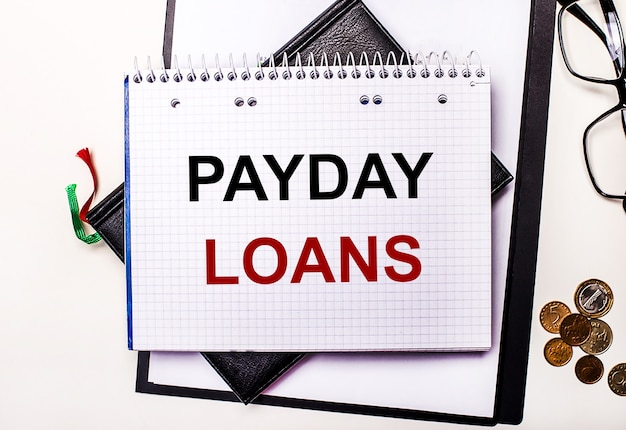 На светлом фоне очки, монеты и блокнот с надписью payday loans.
