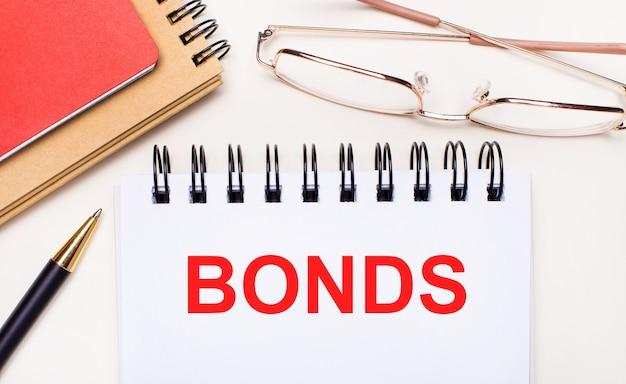 На светлом фоне - очки в золотой оправе, ручка, коричневый и красный блокноты и белый блокнот с текстом bonds. бизнес-концепция