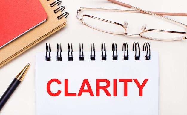 На светлом фоне - очки в золотой оправе, ручка, коричневый и красный блокноты и белый блокнот с текстом clarity. бизнес-концепция