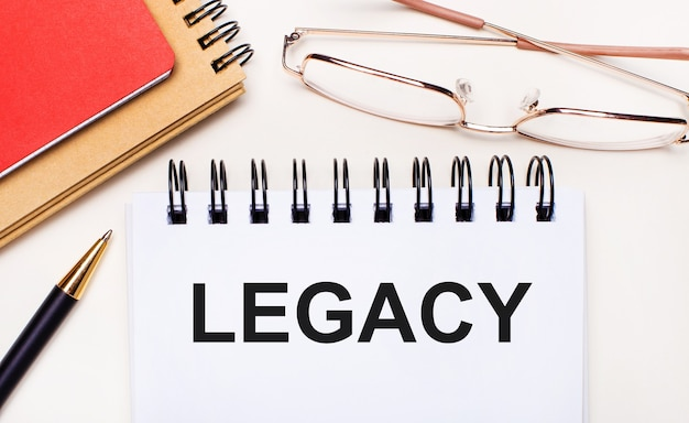 明るい背景-ゴールドフレームのメガネ、ペン、茶色と赤のメモ帳、legacyというテキストの白いノート。ビジネスコンセプト