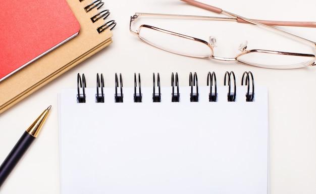 明るい背景-金のフレームのメガネ、クラフトと赤のノートブック、テキストを挿入する場所のある白い空白のノートブック。ビジネスコンセプト