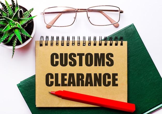 На светлом фоне очки в золотой оправе, цветок в горшке, зеленая тетрадь, красная ручка и коричневая тетрадь с надписью таможенное оформление. бизнес-концепция