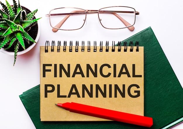 明るい背景に、金枠のメガネ、鍋に花、緑のノート、赤いペン、茶色のノートに「financialplanning」というテキストが付いています。ビジネスコンセプト