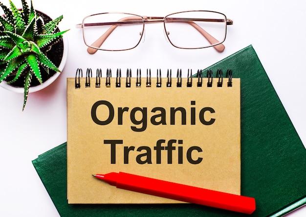 На светлом фоне очки в золотой оправе, цветок в горшке, зеленая тетрадь, красная ручка и коричневая тетрадь с текстом organic traffic. бизнес-концепция
