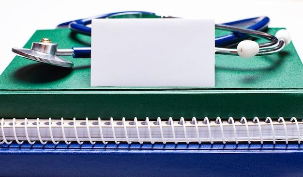 明るい背景に、緑と青のメモ帳、聴診器、テキストを挿入する場所のある白いカード。医療コンセプト