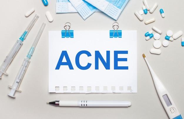 На светлом фоне лежат стетоскоп, электронный термометр, шприц, маска для лица и лист бумаги с надписью acne. медицинская концепция