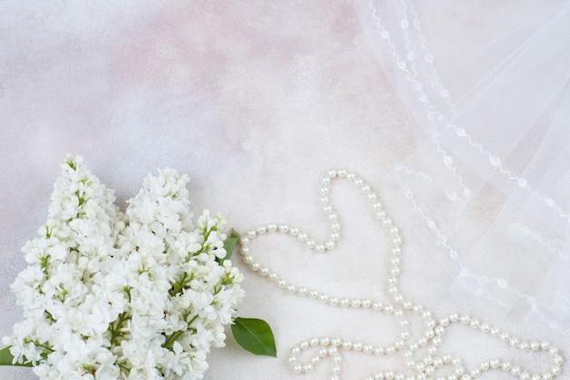 明るい背景にベール、パールビーズ、白いライラックの花束があります。