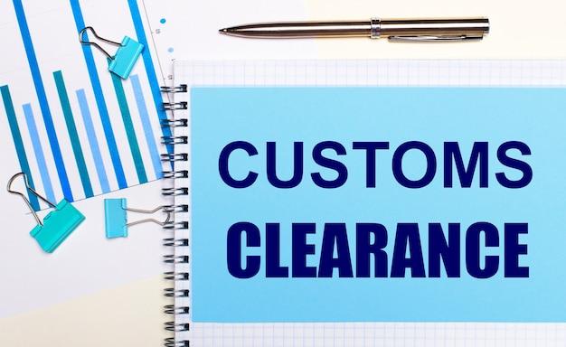 На светлом фоне - голубые схемы, скрепки и лист бумаги с текстом таможенное оформление. вид сверху. бизнес-концепция