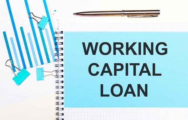 На светлом фоне - голубые схемы, скрепки и лист бумаги с текстом оборотный кредит. вид сверху. бизнес-концепция