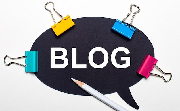 На светлом фоне разноцветные скрепки, белый карандаш и черная бумага с надписью блог. вид сверху