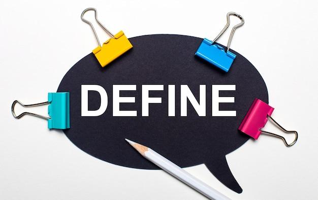 На светлом фоне разноцветные скрепки, белый карандаш и черная бумага с надписью define.