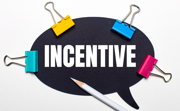 На светлом фоне разноцветные скрепки, белый карандаш и черная бумага с надписью incentive. вид сверху