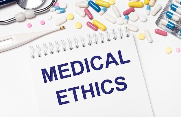 На светлом фоне разноцветные таблетки, стетоскоп, электронный градусник и блокнот с текстом медицинская этика. медицинская концепция.