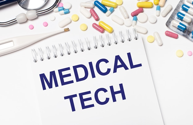 На светлом фоне разноцветные таблетки, стетоскоп, электронный градусник и блокнот с надписью medical tech. медицинская концепция.