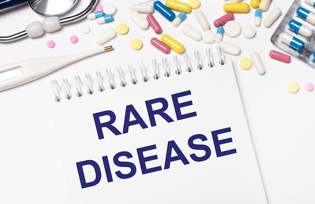 На светлом фоне разноцветные таблетки, стетоскоп, электронный градусник и блокнот с текстом редкое заболевание. медицинская концепция.