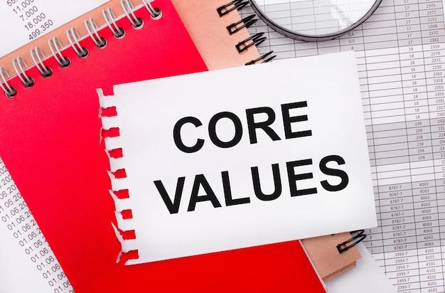 На светлом фоне - отчеты, лупа, коричневые и красные блокноты, а также белый блокнот с текстом core values. бизнес-концепция