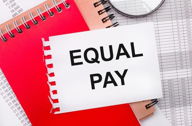 На светлом фоне - отчеты, лупа, коричневые и красные блокноты, а также белый блокнот с надписью equal pay. бизнес-концепция