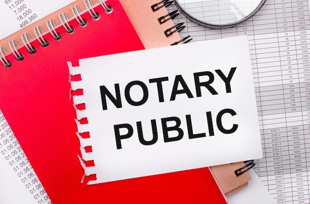 На светлом фоне - отчеты, увеличительное стекло, коричневые и красные блокноты, а также белый блокнот с текстом notary public. бизнес-концепция