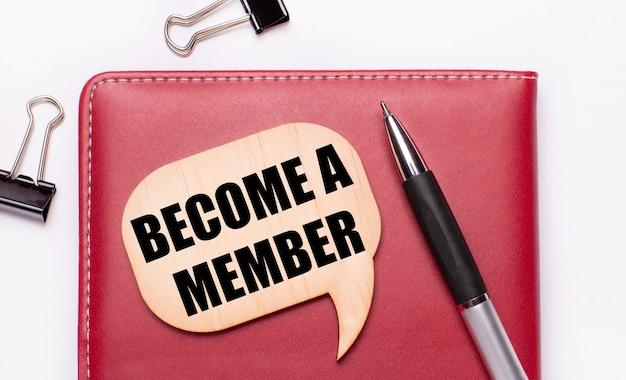 На светлом фоне черные канцелярские скрепки, ручка, блокнот бордового цвета, деревянная доска с надписью стать членом.