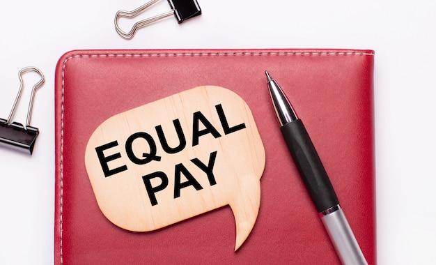 На светлом фоне черные канцелярские скрепки, ручка, блокнот бордового цвета, деревянная доска с надписью equal pay.