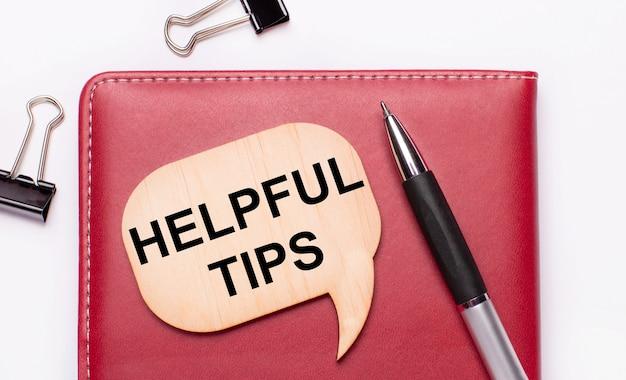 На светлом фоне черные канцелярские скрепки, ручка, блокнот бордового цвета, деревянная доска с текстом полезные советы.