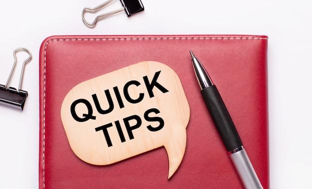 밝은 배경에는 검은색 종이 클립, 펜, 버건디 메모장, quick tips라는 텍스트가 있는 나무 보드가 있습니다.
