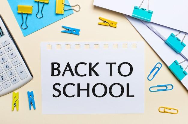 明るい背景には、書類の山、白い電卓、黄色と青のペーパークリップと洗濯バサミ、そして「学校に戻る」というテキストが書かれたノートがあります。