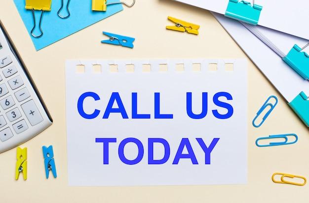 明るい背景には、書類の山、白い電卓、黄色と青のペーパークリップと洗濯バサミ、「call ustoday」というテキストのノートがあります。