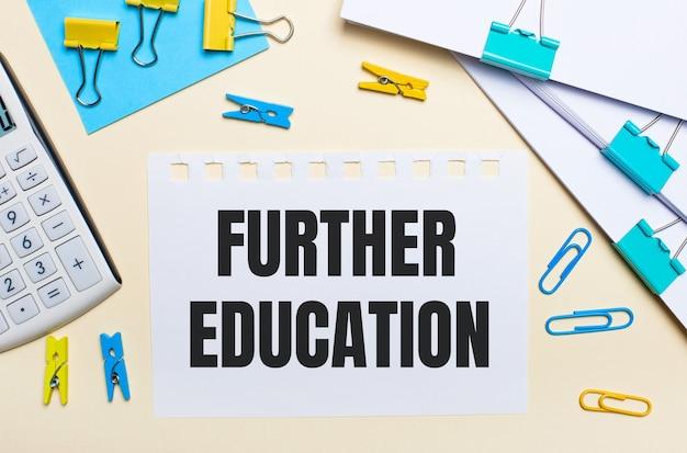 明るい背景には、書類の山、白い電卓、黄色と青のペーパークリップと洗濯バサミ、そして「さらなる教育」というテキストが書かれたノートがあります。