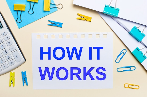 На светлом фоне стопки документов, белый калькулятор, желтые и синие канцелярские скрепки и прищепки, а также блокнот с надписью «как это работает».